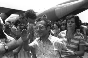 A JOYOUS WAVE OF HAND AND A TENSE SEARCHING LOOK  BY HOME COMING AIR FRANCE HOSTAGES, RESCUED FROM ENTEBBE    AIRPORT.